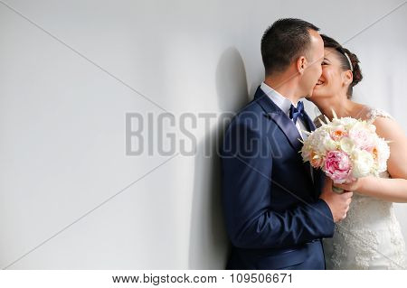 Beautiful Bridal Couple Kissing Next To White Wall