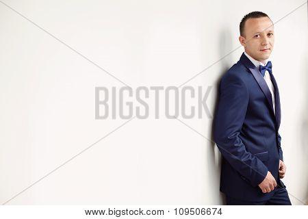 Elegant Groom Posing Next To White Wall Isolated
