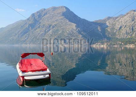 Landscape with the image of boat on a sea and mountains under the background