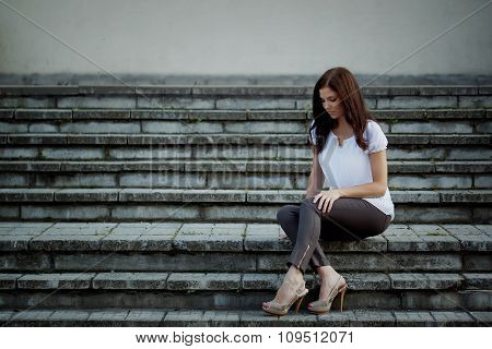 Young Thoughtful Woman Sitting In Stone Stairs