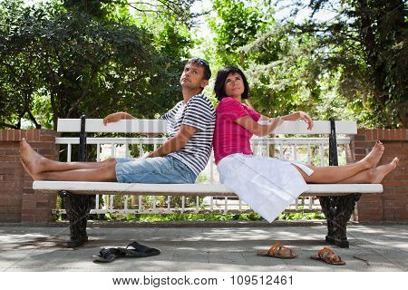 Happy Couple Sitting On Bench In The Park
