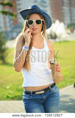girl drinking from a paper bag in the street. smokes. cowboy hat