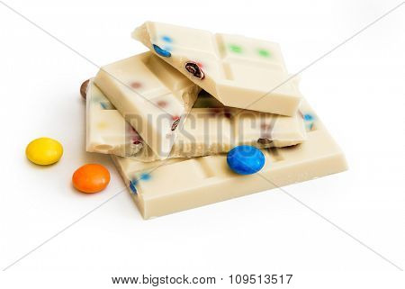 White chocolate with colored pills isolated on white background