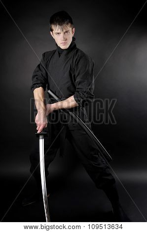 Ninja - Spy, Saboteur, Stealth Assassin Of Feudal Japan. Ninja With Sword Over Dark Background.