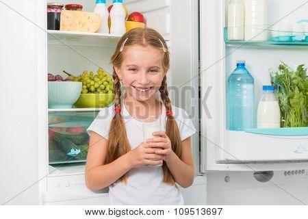 little girl holding a glass of milk near opened fridge