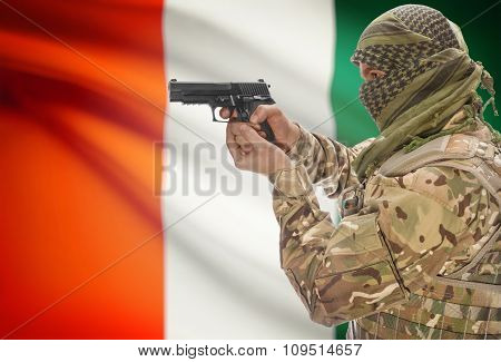Male In Muslim Keffiyeh With Gun In Hand And National Flag On Background - Ivory Coast