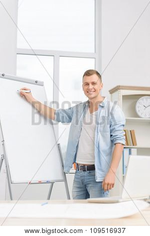 Young businessperson is writing on whiteboard.