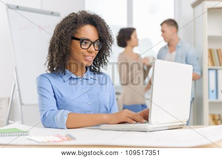 Female employee is working on the laptop.