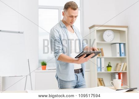 Male employee is working on the tablet.