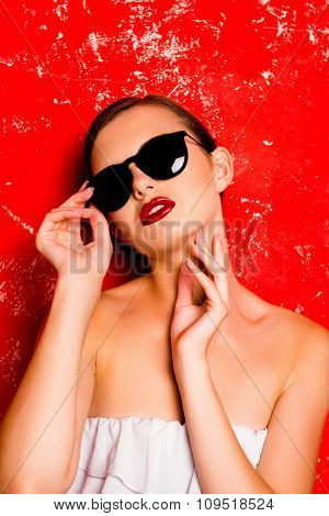 Glamorous Girl With Cool  Spectacles Posturing Against The Red Background