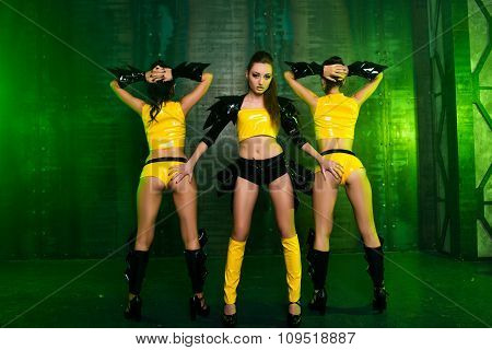 Three Sexy Cute Posing Girls In Stage Yellow Costumes Holding Buttocks
