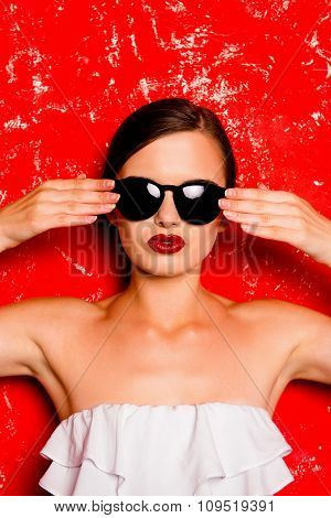 Glamorous Cheerful Girl With Cool  Spectacles Against The Red Background