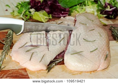 Raw Duck Fillet Is Cut With A Knife