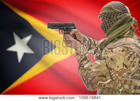 Male In Muslim Keffiyeh With Gun In Hand And National Flag On Background - East Timor