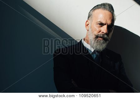 Portrait of bearded man wearing trendy suit and stands against the wall. Horizontal