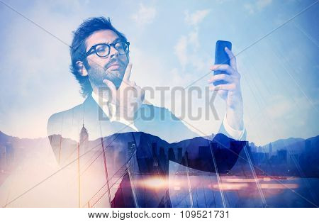 Double exposure of man wearing trendy suit and makes selfe on his smartphone.