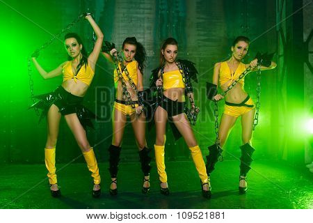 Four Sexy Posing Cute Girls In Stage Costumes With Chains