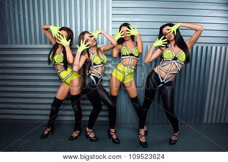 Four Confident Pretty Sexy Girls In Stage Costumes Posturing