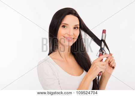 Pretty Young Woman Curling Her Long Hair