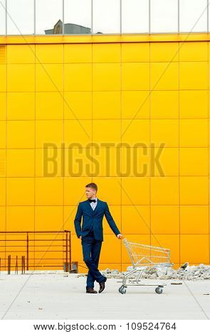 A man in a blue suit with an empty shopping cart outdoors
