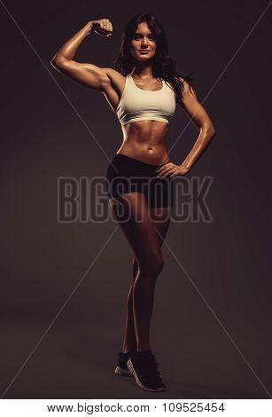 Beautiful Young Athletic Woman Showing Biceps, Studio Shot