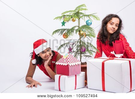 indian girls decorating christmas tree, christmas tree decoration, indian girl preparing for christm