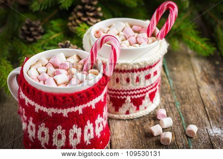 Mugs With Hot Chocolate And Murshmallow And Candy Cane, Wrapped In A Winter Knitted Cup-holders