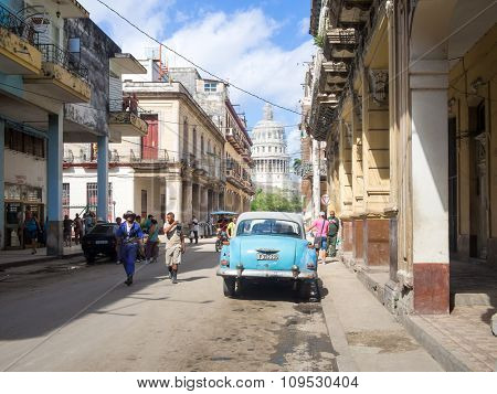 HAVANA,CUBA - NOVEMBER 12, 2015 : Street scene in Old Havana with a view of the Capitol, people and an old american car