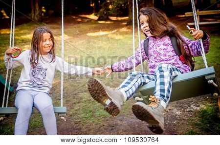 Two Happy Little Girls Swinging On The Swing In A Children Playground