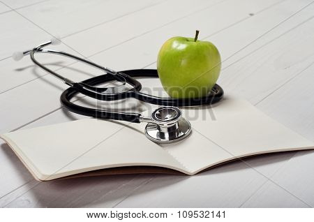 Open Notebook With Blank Pages With Stethoscope And Aplle