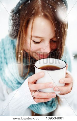 Female Drinking Hot Drink Outdoors In Winter