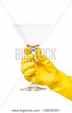 Close up of female hand in yellow protective rubber glove holding clean transparent martini glass
