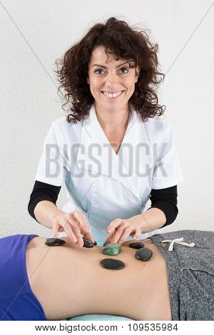 Photo Of Therapist Putting The Hot Stones On The Tummy Of Pretty Woman