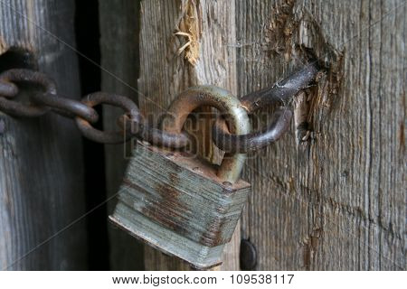 Close Up Of Old Rusty Padlock And Wooden Barn Door.