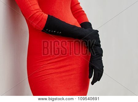 part of  woman in red dress and gloves