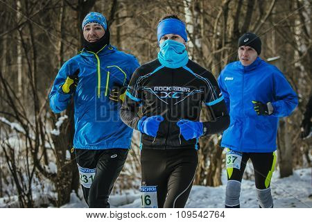 group of young male athletes running together on a snowy Park in December