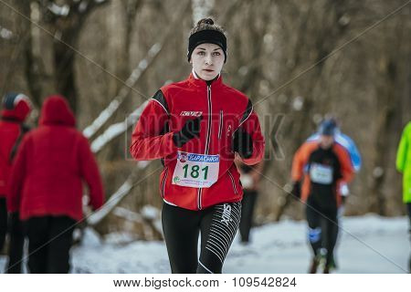 beautiful girl athlete running down alley winter Park