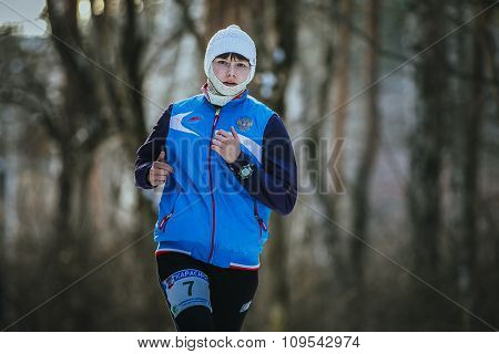 beautiful young woman running in winter forest