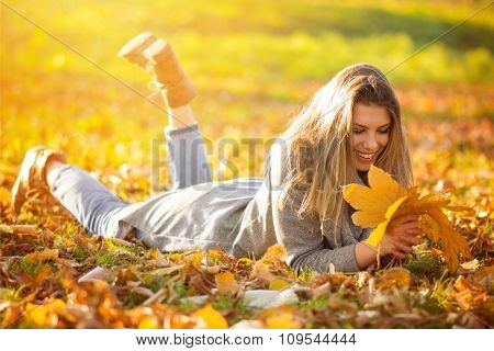 Happy young woman with leaves in park in autumn