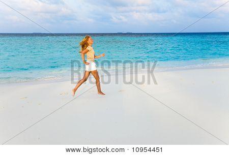 Girl runs at sunset along strip of surf