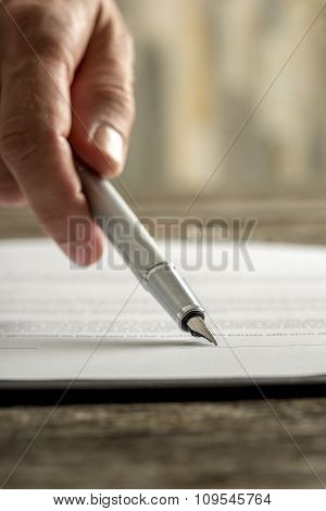 Male Hand Holding Ink Pen Pointing Where To Sign A Contract