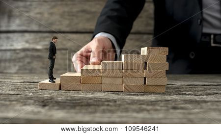 Businessman Building A Staircase For Another Entrepreneur To Climb Up