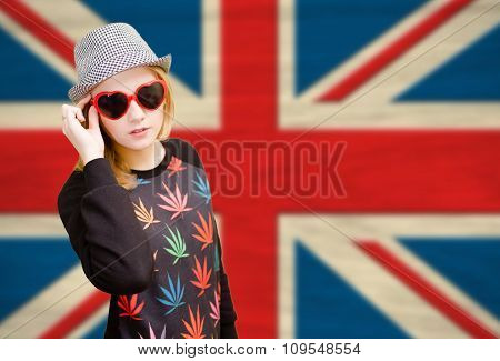 Pretty young woman in sunglasses on english union jack background