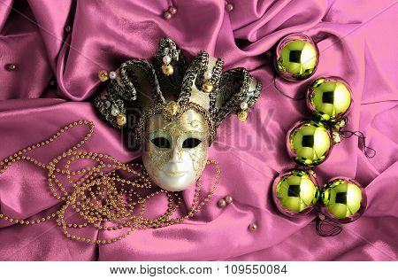 Background Of Golden Christmas Tree Balls With Gold Decorations And Golden Mask On Soft Pink Shiny S