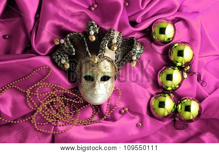 Background Of Golden Christmas Tree Balls With Gold Decorations And Golden Mask On Pink Shiny Silk F