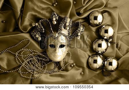 Background Of Golden Christmas Tree Balls With Gold Decorations And Golden Mask On Shiny Silk Fabric
