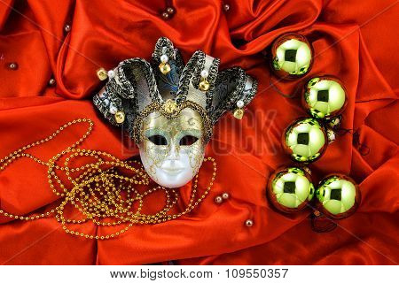 Background Of Golden Christmas Tree Balls With Gold Decorations And Golden Mask On Dark Orange Shiny