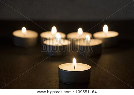 Burning tealights in darkness with texture overlay