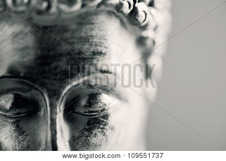 detail of the face of a representation of the buddha with his eyes closed in duotone