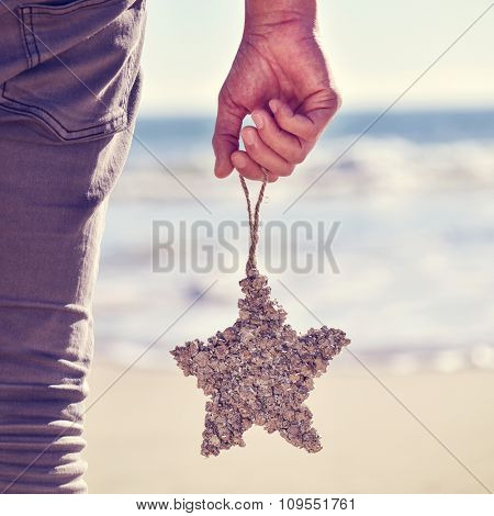 closeup of a young caucasian man seen from behind with a christmas star-shaped ornament hanging from his hand on the beach